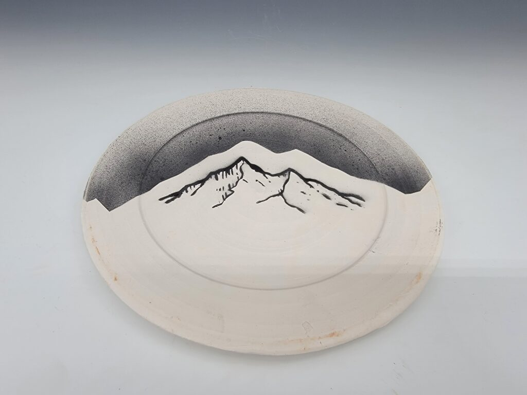 white and grey plate with mountains