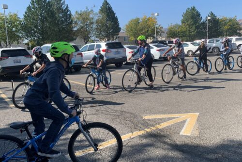 Students at Wright Elementary practice bike safety by riding and using hand signals in the school parking lot.
