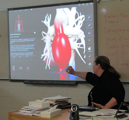 Science teacher at Salt Lake Valley Youth Center in DT, displaying a slide of a heart