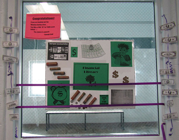 A window display outside of a classroom at Detention showing samples of currency for the Financial Literacy unit
