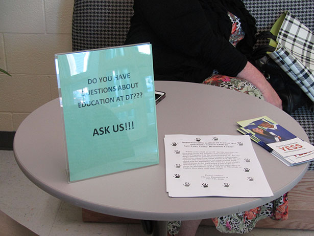 A table inviting visiting family to the Detention Center encouraging them to chat with the teachers regarding their child's school work