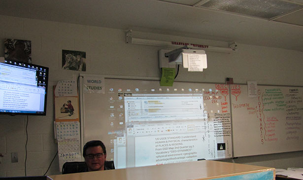 Social Studies teacher at Detention displaying information from his computer onto the white board and a wall-mounted tv