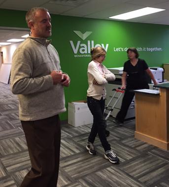 Jason, Associate Director of YESS, Monica, teacher, and Cathy, Registrar, moving school boxes into AIM