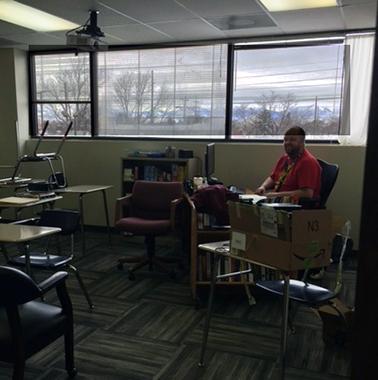 Eric, teacher, sets up his new classroom at AIM