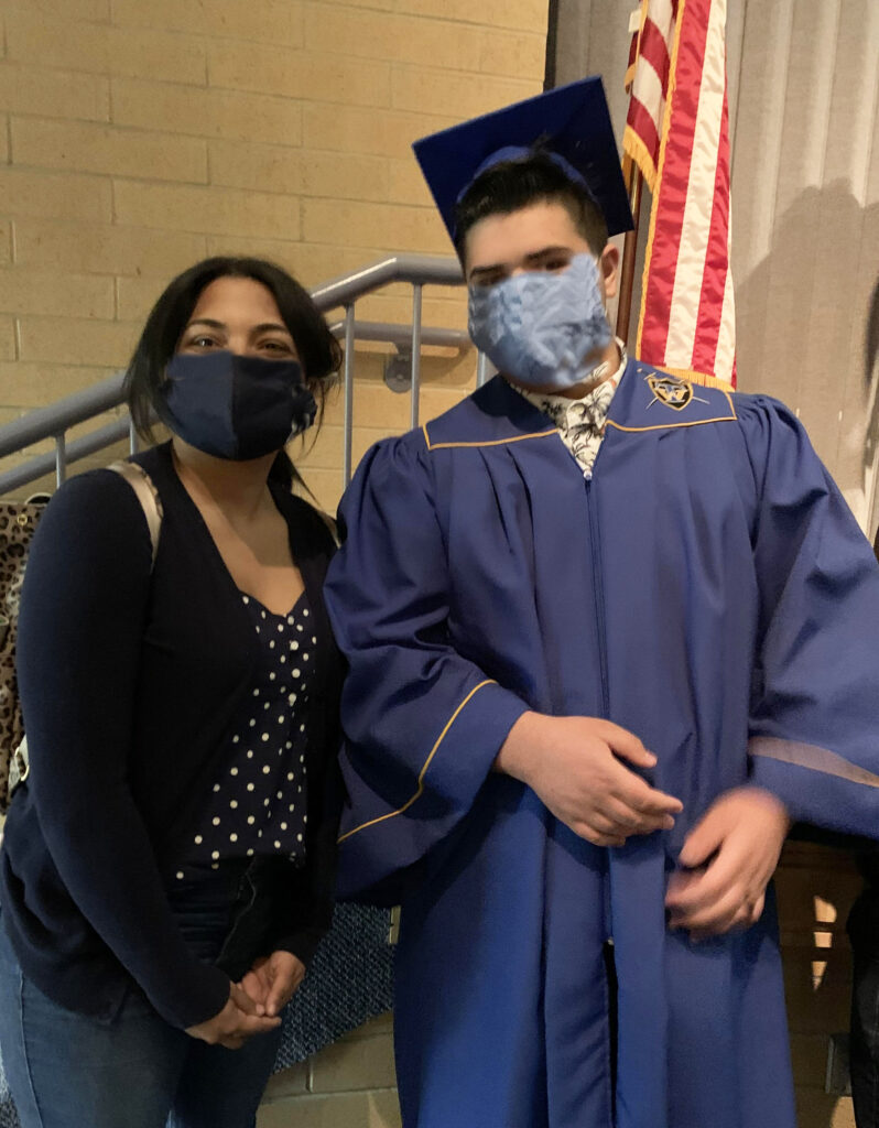 A guest stands with a student who just graduated from high school