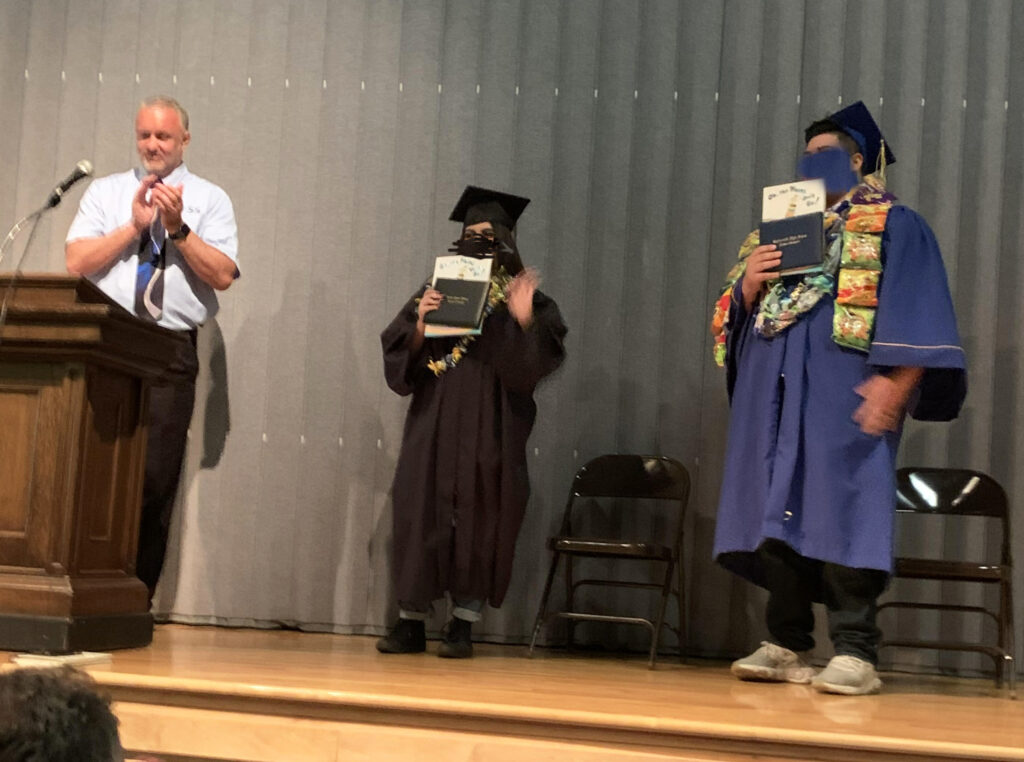 Jason, Associate Director of YESS, congratulates two students on stage at their graduation