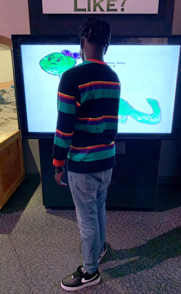 DSI/Gemstone student looking at a hand drawn dinosaur on a computer display at the Museum of Ancient Life at Thanksgiving Point in Lehi, UT